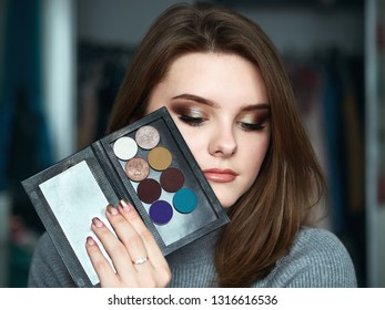 Young beautiful woman with professional make up and hairstyle with cosmetics palette domestic room blurry background