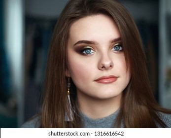 Young beautiful woman with professional make up and hairstyle with domestic room blurry background