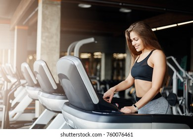 Young beautiful woman programming a threadmill to make her morning jog even harder. Female coach warming up before a long day at work.
