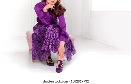 Young and beautiful woman in purple party dress and purple high heel shoes in white room, background with placeholder