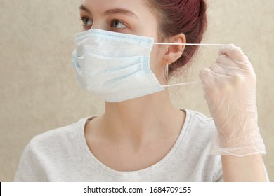 Young beautiful woman put on medical mask for protection against coronavirus contagious disease. on a light background. Medic holding face mask. Preventive measure against coronavirus COVID-19.