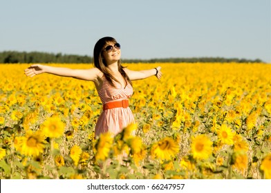 The young beautiful woman quickly stand  on a glade of sunflower, smiles, hands up
