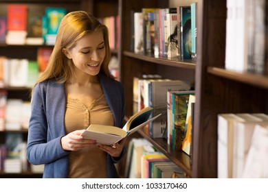 Young beautiful woman reading a book smiling joyfully at the library copyspace knowledge education youth campus college university homework preparation project smart intelligence inspiration.