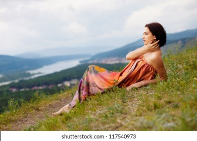 Young beautiful woman reading a book on the hill laying in the grass.