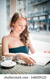 young beautiful woman reading book at the coffee