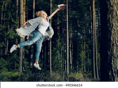 Young beautiful woman reading a book and levitates in the forest