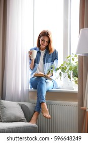 Young beautiful woman reading book and drinking tea at home