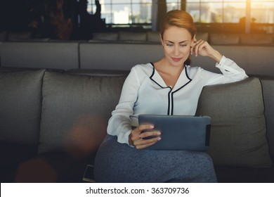 Young beautiful woman reading electronic book via internet on digital tablet while relaxing in coffee shop after work day, modern female watching fashion news on touch pad while waiting order in cafe