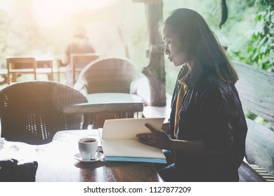 Young beautiful woman reading interesting book in cafe