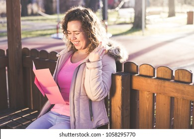 Young beautiful woman reading a love letter at the park.