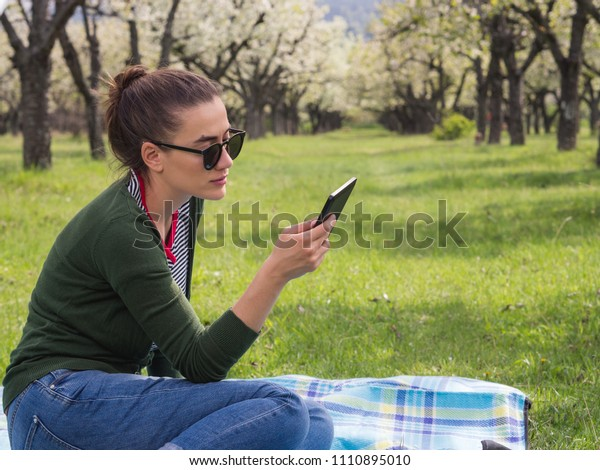 Young beautiful woman reading on her smart phone while relaxing out of town
