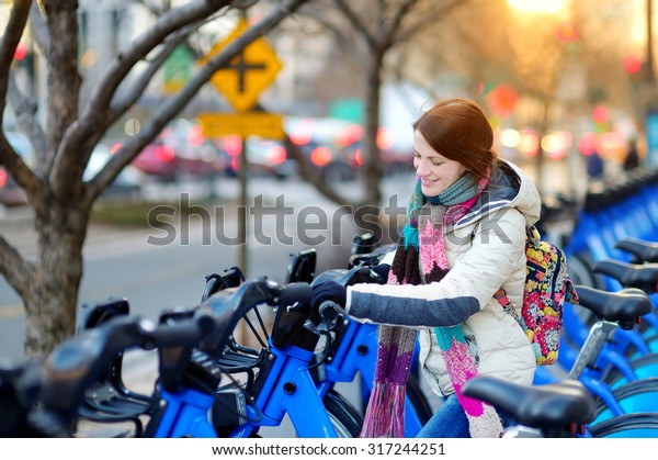 Young beautiful woman ready to rent a city bike in New York, USA