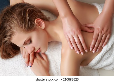 Young beautiful woman receiving back massage and spa treatment