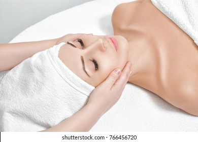 young beautiful woman receiving facial massage at spa salon