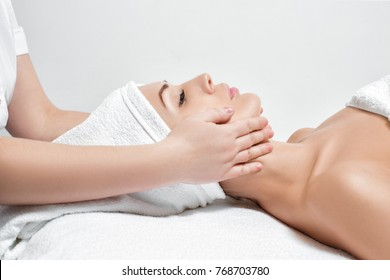 young beautiful woman receiving facial massage at spa salon