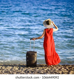 Young beautiful woman in red dress and hat with large suitcase on tropical beach
