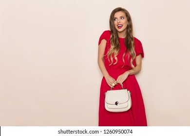 Young beautiful woman in red dress is holding beige purse, looking away and talking. Three quarter length studio shot on beige background.