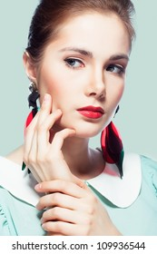 Young beautiful woman with red glamour lips and eye arrow make-up wearing fancy plastic earrings on blue background, retro styled beauty