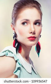 Young beautiful woman with red glamour lips and eye arrow make-up wearing fancy plastic earrings, on colored background, retro styled beauty