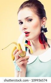 Young beautiful woman with red glamour lips and eye arrow make-up wearing fancy plastic earrings and eating banana, on yellow background, pin-up style