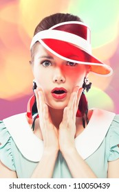 Young beautiful woman with red glamour lips and eye arrow make-up wearing fancy plastic earrings and red sun visor on multicolor background, she is open-mouthed with surprise, retro beauty style