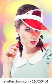 Young beautiful woman with red glamour lips and eye arrow make-up wearing fancy plastic earrings and red sun visor on multicolor background, retro styled beauty