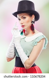 Young beautiful woman with red glamour lips and eye arrow make-up wearing fancy plastic earrings, top hat and white formal gloves, on colored background, retro style
