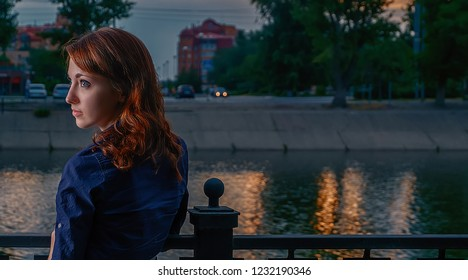 Young beautiful woman with red hair in profile shot against the night Moscow Skyline