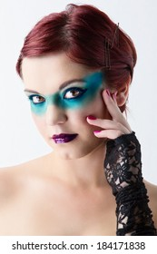 young beautiful woman with red hair wearing emerald green makeup as a mask on studio background
