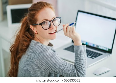 Young beautiful woman with red hair, wearing glasses, working in the office, uses a laptop and mobile phone