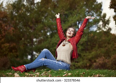 Young beautiful woman in red leather jacket and blue jeans sitting in the autumn park