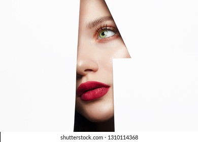 young beautiful woman with red lips makeup into the hole of white paper. make-up artist concept. number one