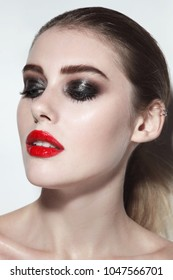 Young beautiful woman with red lipstick and wet smoky eye make-up