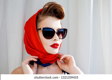 young beautiful woman with red lipstick and a headscarf. Pin-up portrait