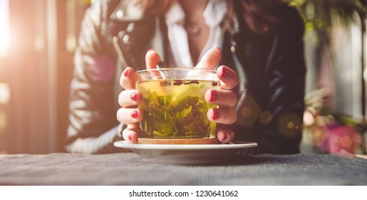 Young beautiful woman with red manicure drinking tea with herbs and lemon in cafe. Close up. Cozy winter morning