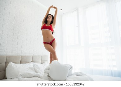 young beautiful woman in red sexy underwear standing in bed in bright bedroom stratching after sleep