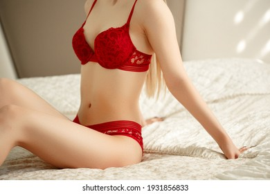 a young beautiful woman in red beautiful underwear meets a sunny morning in the bedroom on the bed. selective focus with a small focus area.