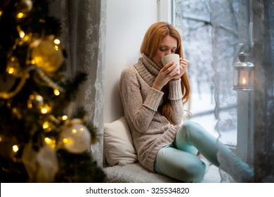 Young beautiful woman with reddish hair sitting home by the window with cup of hot coffee wearing knitted warm sweater. Christmas tree with decorations and lights in the room, snowy winter outside
