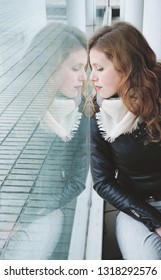 Young beautiful woman reflected in a huge window