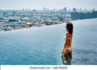 Young beautiful woman relax in swimming pool on rooftop and enjoy cityscape. Summer vacation concept
