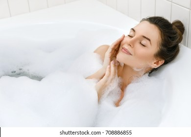 Young and beautiful woman is relaxing in the bath with a foam