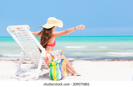 Young beautiful woman relaxing in a chair on a tropical beach