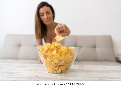 A young beautiful woman relaxing in comfortable cloth on the sofa at home having potato Chips.