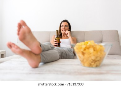 A young beautiful woman relaxing in comfortable cloth on the sofa at home having Beer and potato Chips.
