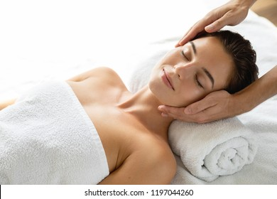Young and beautiful woman is relaxing during facial massage session