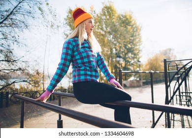 Young beautiful woman relaxing during street workout sitting on parallel bars at calisthenics park, looking off the camera