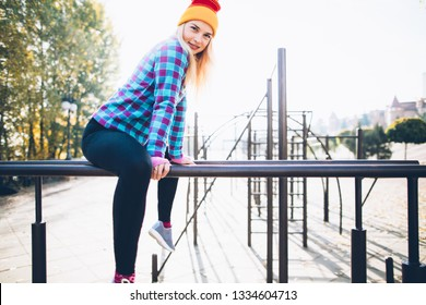Young beautiful woman relaxing during street workout sitting on parallel bars at calisthenics park, looking at camera