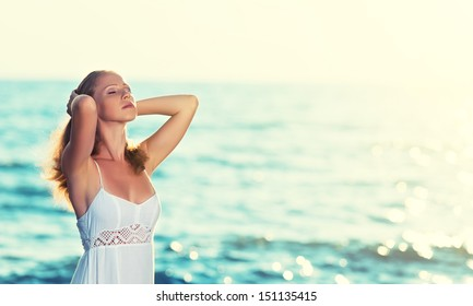 young beautiful woman is relaxing and enjoying the sea with closed eyes