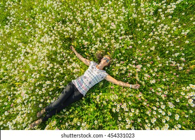 Young beautiful woman relaxing in the field with flowers. Overhead view.