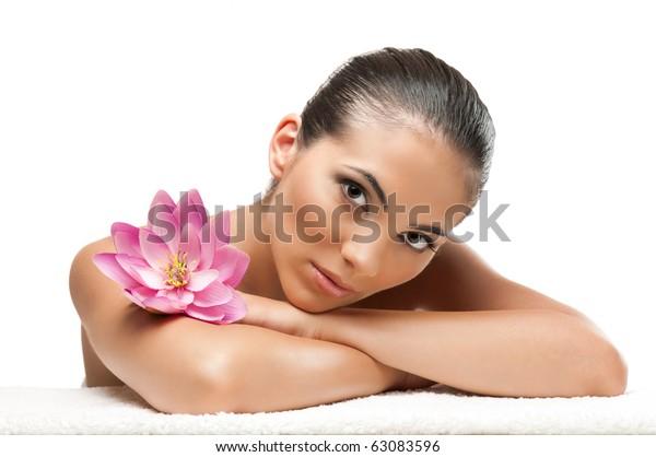 Junge schöne Frau, die sich mit Lotusblume im Spa entspannt, einzeln auf weißem Hintergrund, professionelle Schönheit
